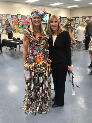teacher and teacher pose in front of art displays